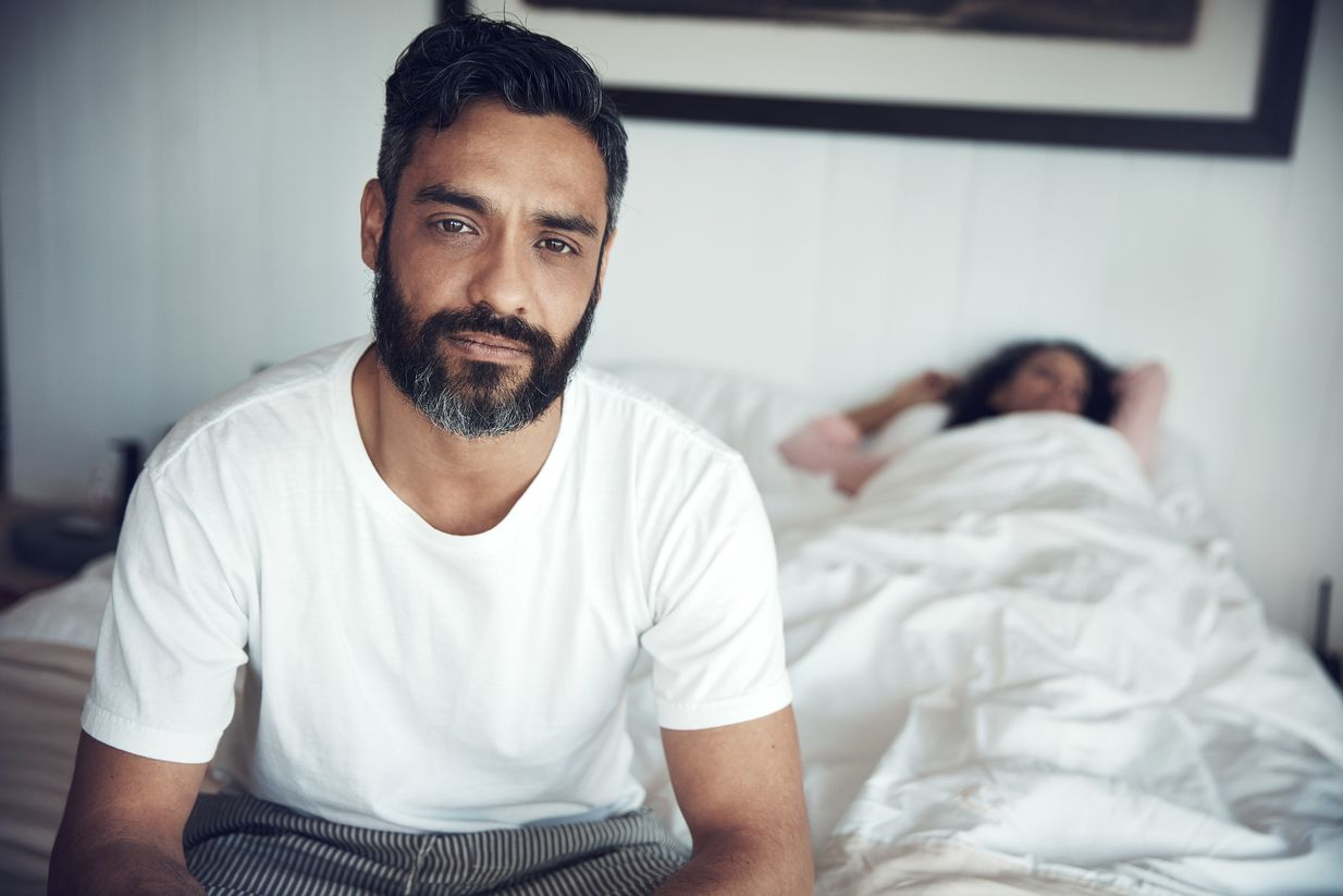 Concerned man sitting on a bed in front of his sleeping partner